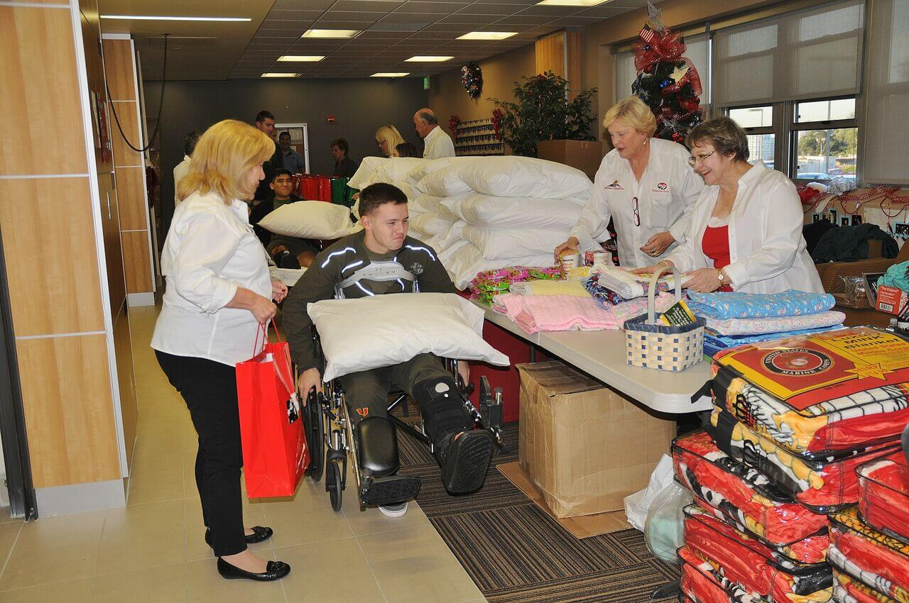 Warrior Foundation-Freedom Station volunteers providing an injured warrior with gifts